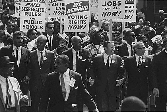 Civil rights marchers carrying signs demanding voting rights and the end of segregated schools