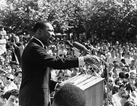 Martin Luther King at a podium addressing a crowd at a civil rights demonstration